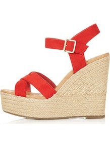 Whispered Cross Over Wedges - predominant colour: true red; occasions: casual, evening, work, holiday; material: leather; heel height: high; ankle detail: ankle strap; heel: wedge; toe: open toe/peeptoe; style: standard; finish: plain; pattern: plain
