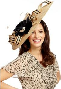Caramel Statement Hatinator - predominant colour: camel; secondary colour: black; occasions: evening, occasion; type of pattern: large; style: wide brimmed; size: large; material: macrame/raffia/straw; pattern: plain; trends: sculptural frills; embellishment: corsage