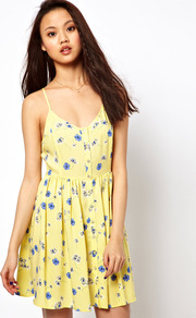 Daisy Print Sun Dress - length: mid thigh; sleeve style: spaghetti straps; fit: fitted at waist; style: sundress; waist detail: twist front waist detail/nipped in at waist on one side/soft pleats/draping/ruching/gathering waist detail; secondary colour: pale blue; predominant colour: primrose yellow; occasions: casual, holiday; neckline: scoop; fibres: viscose/rayon - 100%; hip detail: soft pleats at hip/draping at hip/flared at hip; back detail: crossover; sleeve length: sleeveless; pattern type: fabric; pattern size: small & light; pattern: florals; texture group: jersey - stretchy/drapey