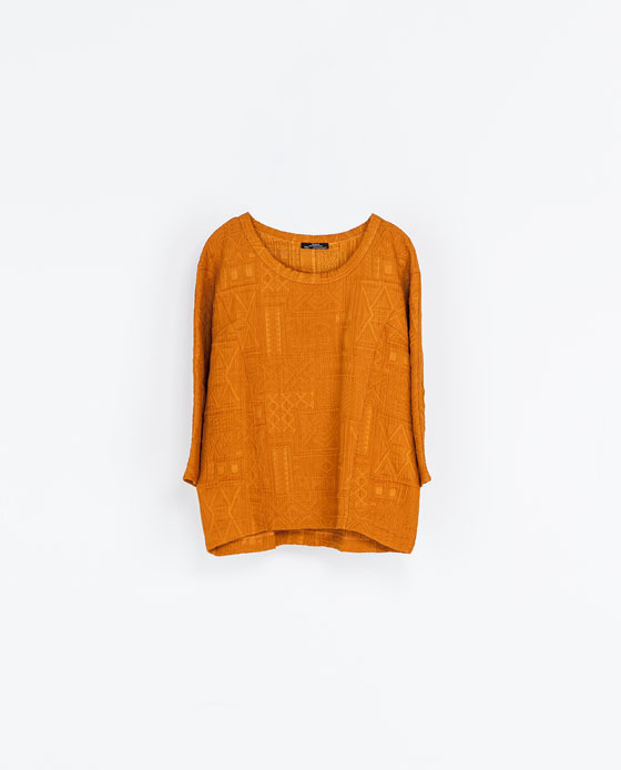 Round Neck T Shirt - neckline: round neck; pattern: plain; predominant colour: bright orange; occasions: casual; length: standard; style: top; fibres: polyester/polyamide - stretch; fit: loose; back detail: longer hem at back than at front; sleeve length: 3/4 length; sleeve style: standard; pattern type: fabric; pattern size: light/subtle; texture group: woven light midweight; trends: oversized structure; season: a/w 2013