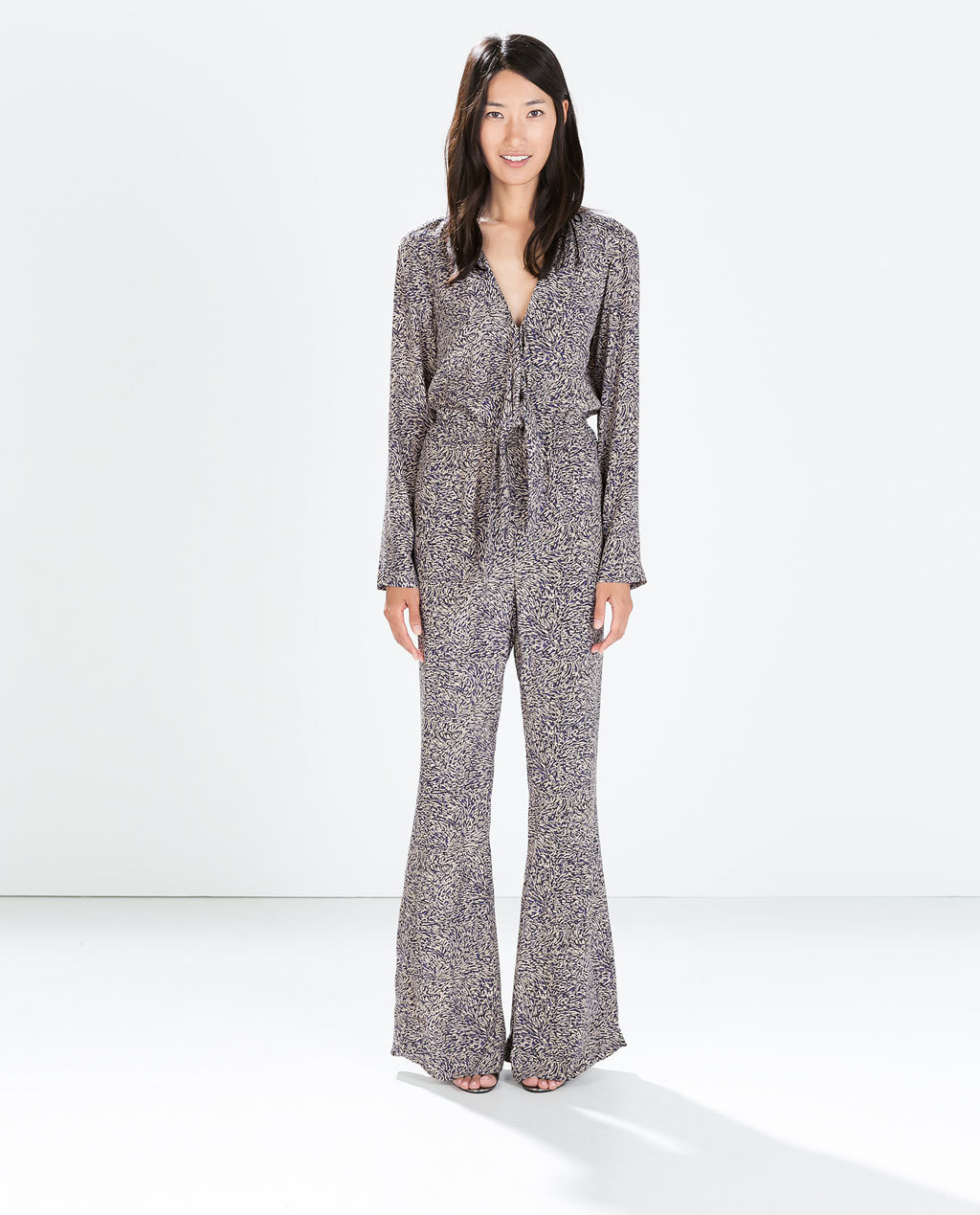 Long Sleeved Bell Bottom Jumpsuit - length: standard; neckline: low v-neck; waist detail: belted waist/tie at waist/drawstring; predominant colour: navy; occasions: casual, evening; fit: body skimming; fibres: viscose/rayon - 100%; sleeve length: long sleeve; sleeve style: standard; style: jumpsuit; pattern type: fabric; pattern size: light/subtle; pattern: patterned/print; texture group: woven light midweight; season: a/w 2014