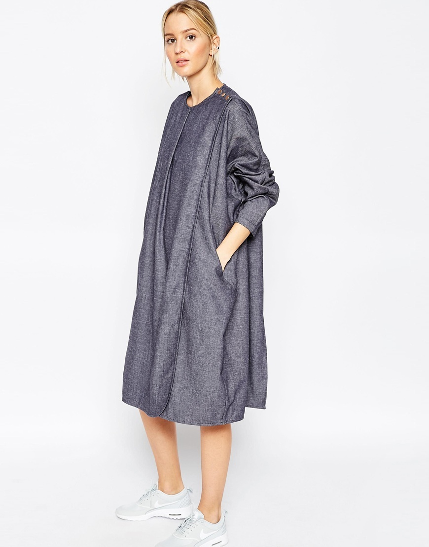 Ovoid Wrap Dress In Chambray Denim Blue - style: smock; length: below the knee; neckline: round neck; sleeve style: dolman/batwing; fit: loose; pattern: plain; hip detail: front pockets at hip; predominant colour: navy; occasions: casual, creative work; fibres: cotton - 100%; sleeve length: 3/4 length; texture group: denim; pattern type: fabric; season: a/w 2015; wardrobe: basic