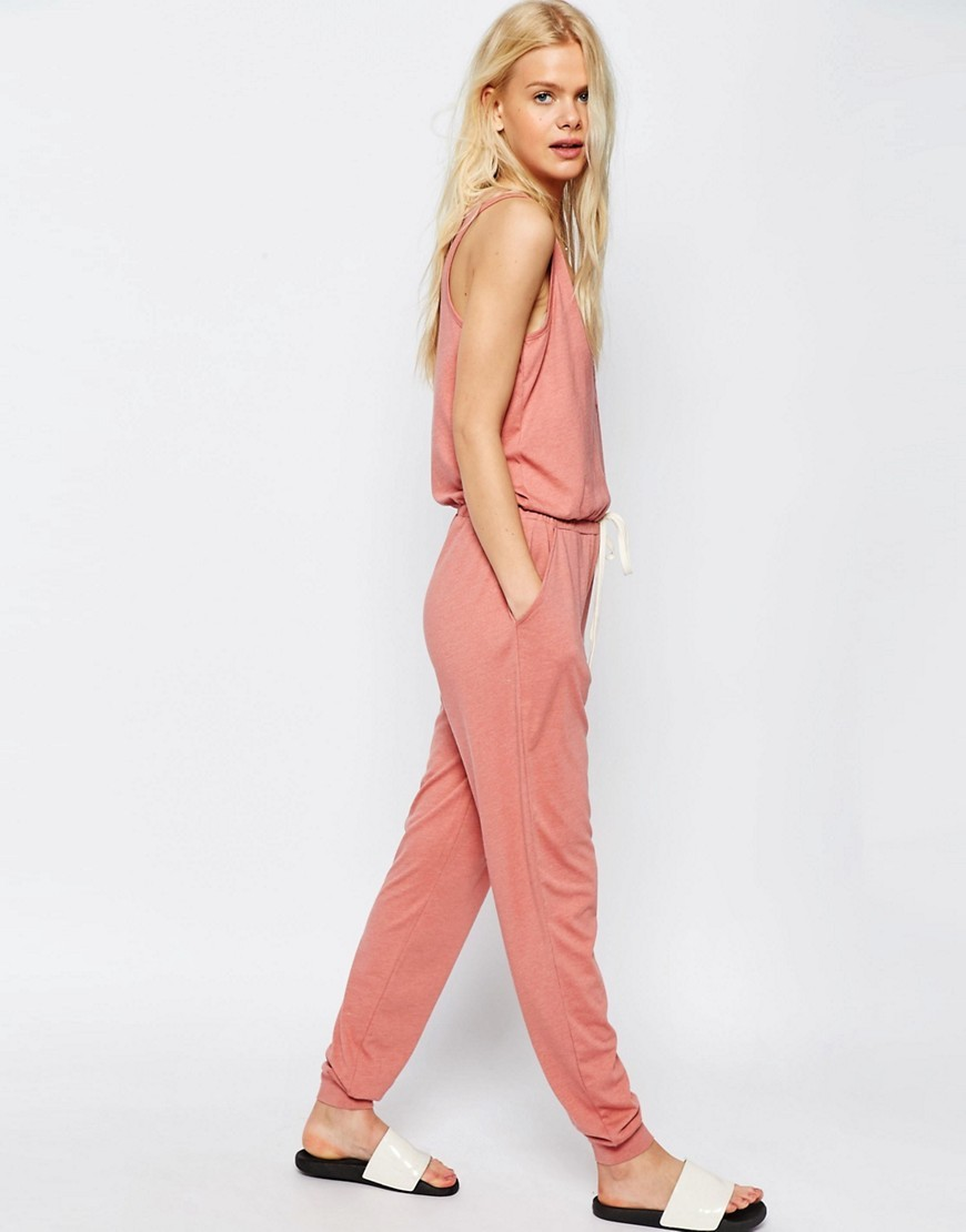 Jersey Jumpsuit With Button Detail And Tie Waist Salmon - length: standard; neckline: round neck; pattern: plain; sleeve style: sleeveless; waist detail: fitted waist; predominant colour: coral; occasions: casual, holiday; fit: fitted at waist & bust; fibres: cotton - mix; sleeve length: sleeveless; style: jumpsuit; pattern type: fabric; texture group: jersey - stretchy/drapey; season: s/s 2016; wardrobe: holiday; embellishment location: bust