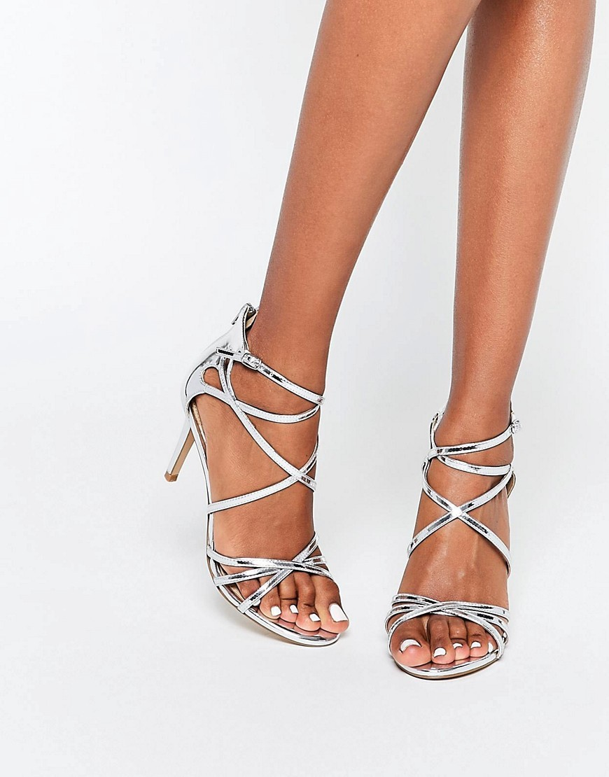 By Dune Minita Silver Strappy Heeled Sandals Silver Pu - predominant colour: silver; occasions: evening, occasion; material: faux leather; heel height: mid; ankle detail: ankle strap; heel: stiletto; toe: open toe/peeptoe; style: strappy; finish: metallic; pattern: plain; season: s/s 2016; wardrobe: event