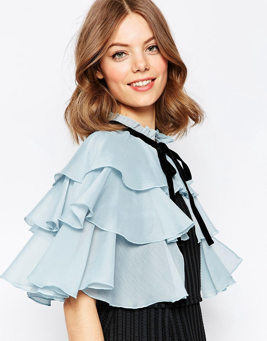Tiered Frill Cape Blue - neckline: round neck; pattern: plain; length: cropped; predominant colour: pale blue; secondary colour: black; style: cape style; fibres: polyester/polyamide - 100%; occasions: occasion; fit: loose; sleeve length: half sleeve; texture group: sheer fabrics/chiffon/organza etc.; pattern type: fabric; sleeve style: cape/poncho sleeve; embellishment: bow; season: s/s 2016; wardrobe: event