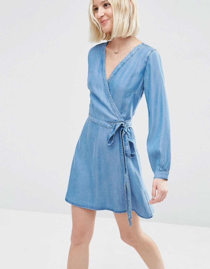 Denim Soft Wrap Mini Dress In Mid Wash Blue - style: faux wrap/wrap; length: mid thigh; neckline: v-neck; pattern: plain; waist detail: belted waist/tie at waist/drawstring; predominant colour: denim; occasions: casual; fit: body skimming; fibres: viscose/rayon - 100%; sleeve length: long sleeve; sleeve style: standard; texture group: denim; pattern type: fabric; season: s/s 2016; wardrobe: basic