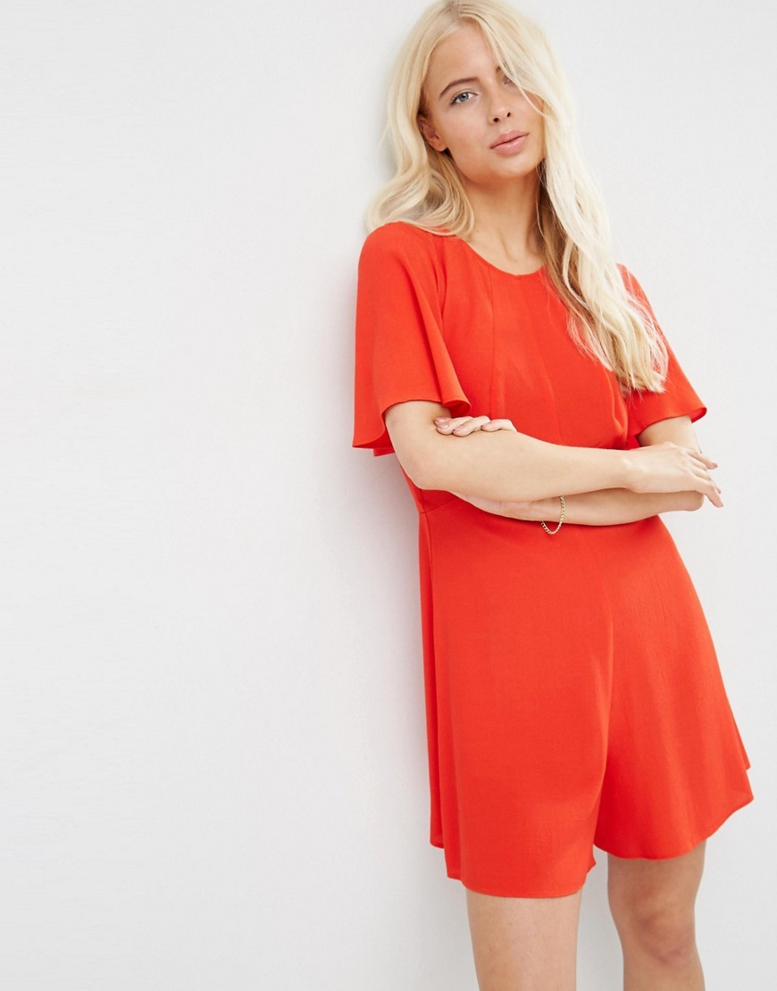 Flutter Sleeve Playsuit Red - neckline: round neck; sleeve style: angel/waterfall; fit: loose; pattern: plain; length: short shorts; predominant colour: bright orange; occasions: casual, holiday; fibres: viscose/rayon - 100%; sleeve length: short sleeve; style: playsuit; pattern type: fabric; texture group: other - light to midweight; season: s/s 2016; wardrobe: holiday