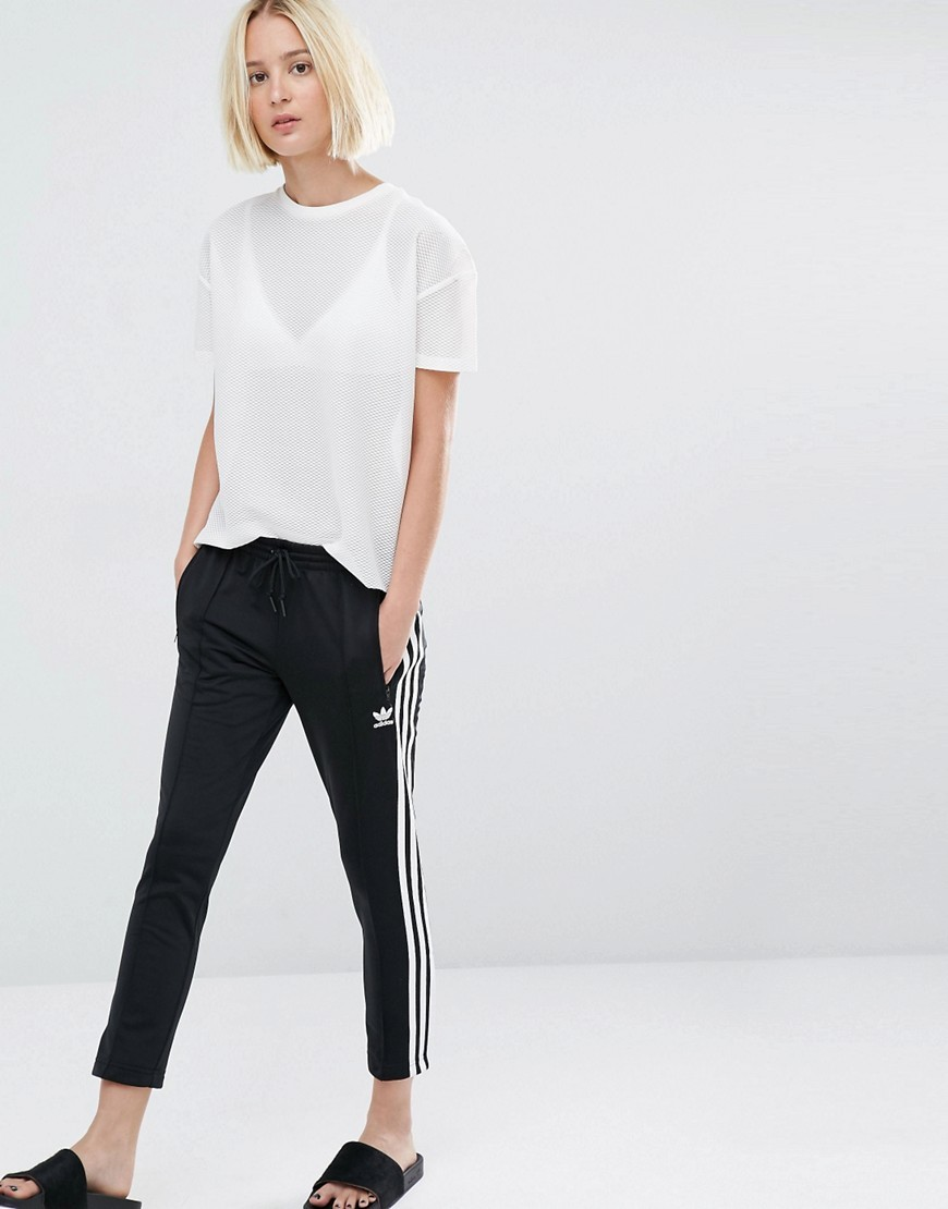 Originals Three Stripe Cigarette Trousers Black - style: tracksuit pants; waist detail: elasticated waist; waist: mid/regular rise; predominant colour: black; length: ankle length; fibres: cotton - stretch; trends: monochrome; fit: slim leg; pattern type: fabric; pattern: patterned/print; texture group: jersey - stretchy/drapey; occasions: activity; pattern size: light/subtle (bottom); season: s/s 2016