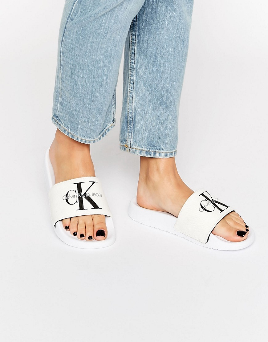Jeans Chantal White Slider Flat Sandals White Canvas - predominant colour: white; occasions: casual, holiday; material: fabric; heel height: flat; heel: block; toe: open toe/peeptoe; style: slides; finish: plain; pattern: patterned/print; season: s/s 2016; wardrobe: highlight