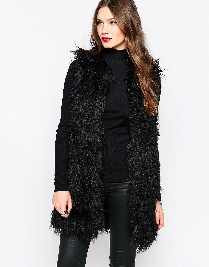 Chicago Faux Fur Gilet In Black Black - pattern: plain; sleeve style: sleeveless; style: gilet; collar: shawl/waterfall; fit: slim fit; predominant colour: black; occasions: casual; length: mid thigh; sleeve length: sleeveless; texture group: fur; collar break: low/open; pattern type: fabric; fibres: viscose/rayon - mix; season: a/w 2016; wardrobe: highlight
