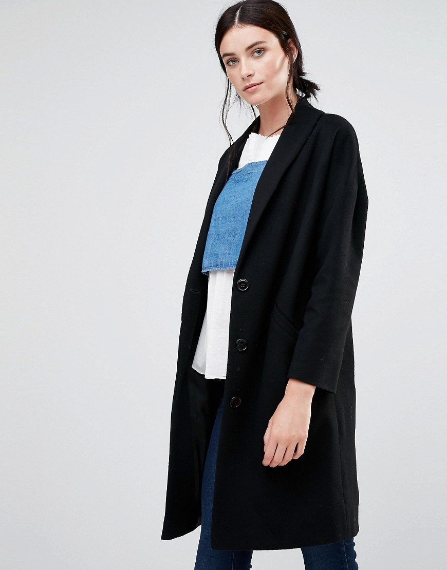 Ovoid Ema Coat In Black Black - pattern: plain; fit: loose; style: single breasted; length: on the knee; collar: standard lapel/rever collar; predominant colour: black; occasions: casual; fibres: wool - mix; sleeve length: long sleeve; sleeve style: standard; collar break: medium; pattern type: fabric; texture group: woven bulky/heavy; wardrobe: basic; season: a/w 2016