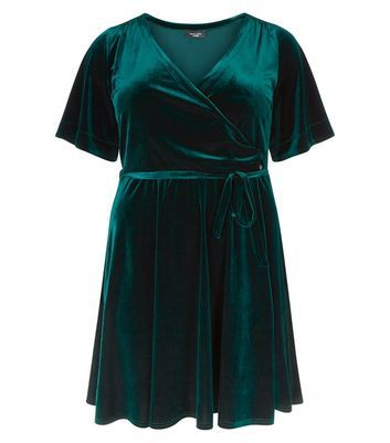 Curves Dark Green Velvet Wrap Dress - style: faux wrap/wrap; length: mid thigh; neckline: v-neck; sleeve style: angel/waterfall; pattern: plain; waist detail: belted waist/tie at waist/drawstring; predominant colour: dark green; occasions: evening; fit: fitted at waist & bust; fibres: polyester/polyamide - stretch; hip detail: subtle/flattering hip detail; sleeve length: short sleeve; pattern type: fabric; texture group: velvet/fabrics with pile; season: a/w 2016; wardrobe: event; trends: velvet