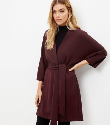 Burgundy Belted Kimono Jacket - pattern: plain; collar: round collar/collarless; fit: loose; predominant colour: burgundy; occasions: casual, creative work; fibres: polyester/polyamide - 100%; length: mid thigh; waist detail: belted waist/tie at waist/drawstring; sleeve length: 3/4 length; texture group: crepes; collar break: medium; pattern type: fabric; style: fluid/kimono; sleeve style: cape/poncho sleeve; season: a/w 2016; wardrobe: highlight