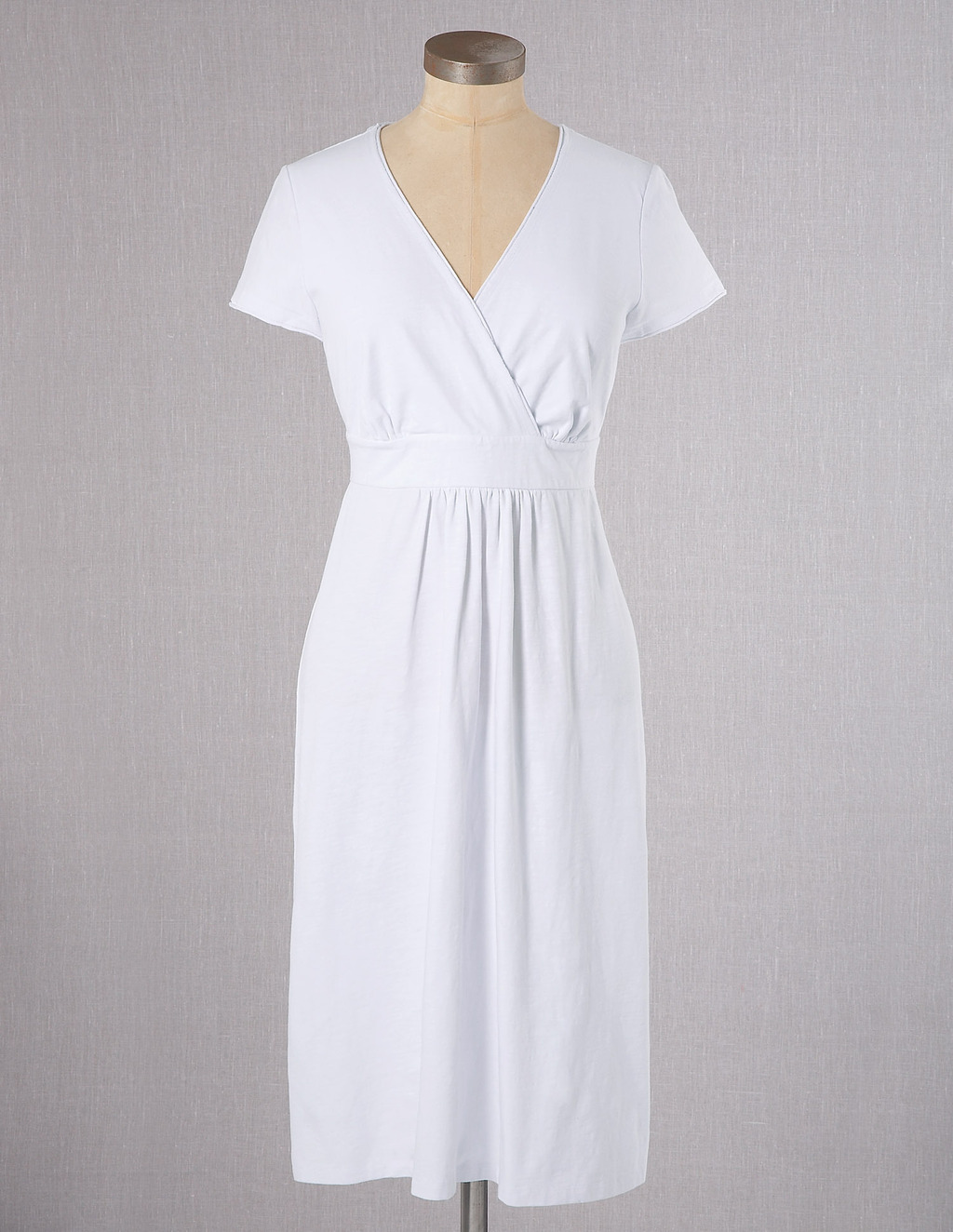 Casual Jersey Dress - style: faux wrap/wrap; neckline: v-neck; fit: empire; pattern: plain; waist detail: fitted waist; bust detail: subtle bust detail; predominant colour: white; occasions: casual, holiday; length: on the knee; fibres: cotton - stretch; hip detail: sculpting darts/pleats/seams at hip; sleeve length: short sleeve; sleeve style: standard; pattern type: fabric; texture group: jersey - stretchy/drapey; season: s/s 2013